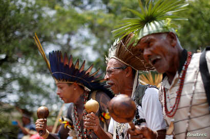 FILE - Indigenous people from various tribes dance as they wait to deliver a letter to Brazil's President-elect Jair Bolsonaro at a transitional government building in Brasilia, Brazil, Dec. 6, 2018.