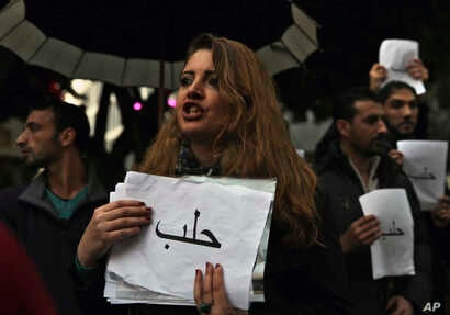 "A Lebanese woman holds a paper with ""Aleppo"" written in Arabic as she chants slogans during a sit-in to express solidarity with residents of the Syrian city of Aleppo, in downtown Beirut, Lebanon, Dec. 13, 2016."