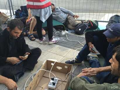 Outside Vienna train station, aid workers provide what many refugees want most: electricity to charge mobile phones that kept them alive and on track so far, Sept. 15, 2015. (Photo: H. Murdock / VOA)