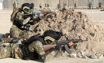 Members of Iraqi Popular Mobilization Forces demonstrate their skills during a military exercise at a graduation ceremony in Basra, Iraq Jan. 31, 2019.