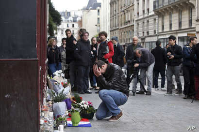 A man holds his head in his hands as he lays flowers in front of the Carillon cafe, in Paris, Nov. 14, 2015.