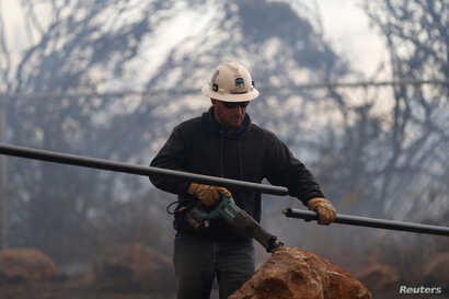 A Pacific Gas & Electric lineman cuts a downed power line during the Camp Fire in Paradise, California, Nov. 8, 2018.