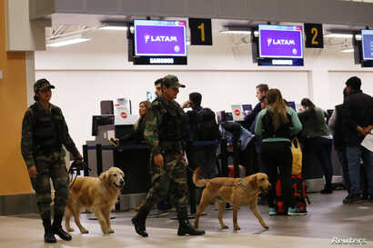 Police patrol with dogs near the LATAM airlines gates in Jorge Chavez airport in Callao, Peru, Aug. 16, 2018.