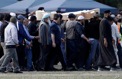 Mourners carry the body of a victim of the March 15 mosque shootings for burial at the Memorial Park Cemetery in Christchurch, New Zealand, March 20, 2019.