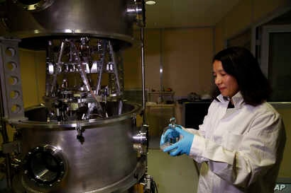 FILE - Executive Secretary of the Consultative Committee for Mass and related quantities (CCM) Dr. Hao Fang holds a weight at the International Bureau of Weights and Measures, in Sevres, near Paris, Oct. 17, 2018. The golf ball-sized metal cylinder a...