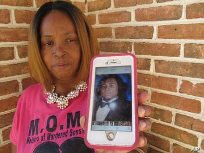 Barbara O'Neal holds her smartphone, which displays a photograph of her slain son, Alan O'Neal Jr., in Savannah, Ga., July 31, 2017. O'Neal started the group Mothers of Murdered Sons in Savannah after her 20-year-old son was fatally shot during an at...