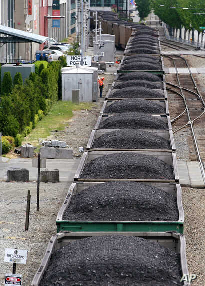 FILE - A train hauling coal runs between office buildings, condos and the downtown waterfront in Seattle, Wash. Scientific consensus holds that the emission of greenhouse gases from the burning of fossil fuels is the main cause of global warming.