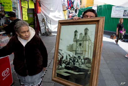 Rosa Maria Ubaldo Lopez looks at an 1910 photograph of her neighborhood, where the oldest building is located in Mexico City, Sept. 10, 2018.