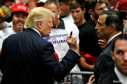 FILE - Republican U.S. presidential candidate Donald Trump, left, speaks with U.S. Representative Darrell Issa, right, after a rally with supporters in San Diego, California, May 27, 2016.