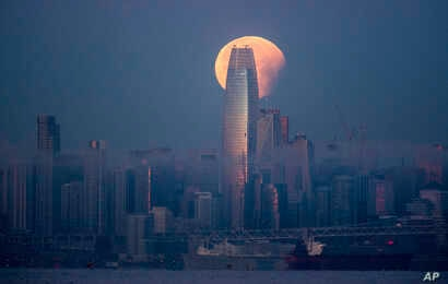 A partially-eclipsed super blue blood moon sets behind the Salesforce Tower, Jan. 31, 2018, in San Francisco, California.