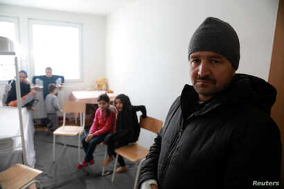 Afghan refugee Najibullah, 30, is pictured with his children at the camp for refugees and migrants in the Belgrade suburb of Krnjaca, Serbia, Jan. 16, 2018.