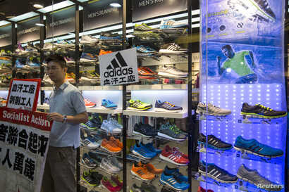 A labor activist stands outside an Adidas store with a protest sign, in support of a strike by workers of Yue Yuen Industrial Holdings, pasted on its shop window during International Labour Day in Hong Kong May 1, 2014.