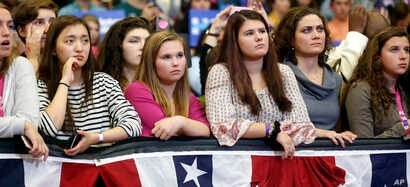 Young women listen to first lady Michelle Obama speak during a campaign rally for Democratic presidential candidate Hillary Clinton in Manchester, N.H., Oct. 13, 2016.