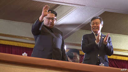 This picture captured from video footage by Korea Pool reporters shows North Korean leader Kim Jong Un (L) and South Korea's Culture, Sports and Tourism Minister Do Jong-whan (R) during a rare concert by South Korean musicians at the 1,500-seat East ...