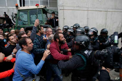 Civil guards clear people away from the entrance of a sports center, assigned to be a referendum polling station by the Catalan government in Sant Julia de Ramis, near Girona, Spain, Oct. 1, 2017.