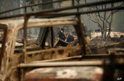 Sheriff's deputies look at a spot that may contain human remains at a home burned in the Camp Fire, Nov. 15, 2018, in Magalia, Calif.