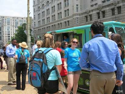 Outside EPA headquarters food vendor hands out free ice cream alongside environmental activists who help passersby register comments online about the climate initiative, (Rosanne Skirble/VOA).