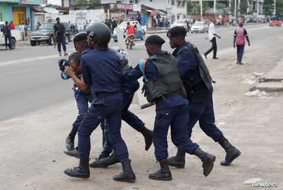 FILE - Policemen detain a protester after the Sunday Mass prayer in front of Notre Dame Cathedral in Kinshasa, Democratic Republic of Congo, Feb. 25, 2018.
