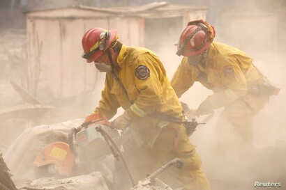 Cal Fire firefighters comb through a house destroyed by the Camp Fire in Paradise, California, U.S., Nov. 13, 2018.