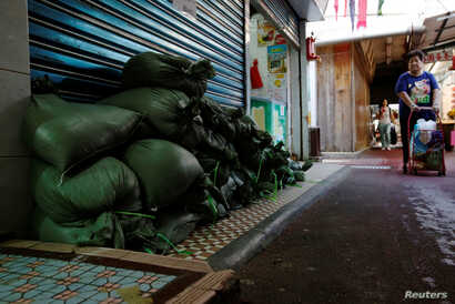 Sandbags are put in front of a shop at Lei Yue Mun, a village as one of the several areas at-risk, as Typhoon Mangkhut approaches Hong Kong, China, Sept. 14, 2018.