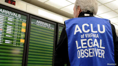 An American Civil Liberties Union legal observer watches a flight arrivals board, as dozens of pro-immigration demonstrators greeted international passengers arriving at Dulles International Airport, to protest President Donald Trump's executive orde...