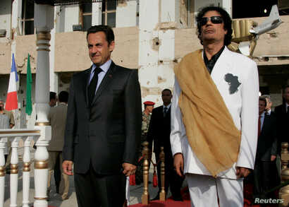 FILE - Libya's President  Muammar Gadhafi (R) and his counterpart from France Nicolas Sarkozy listen to national anthems at Bab Azizia Palace in Tripoli, July 25, 2007.