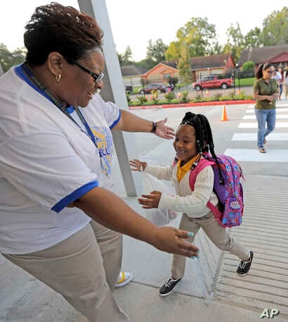 School secretary Demitra Cain, left, greets Tahja Hollerman, 5, for her first day of kindergarten at Codwell Elementary School, Sept. 11, 2017, in Houston.