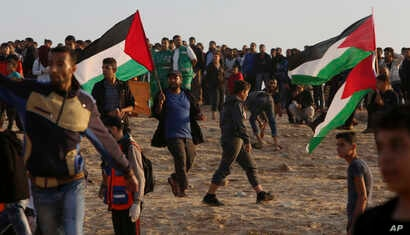 Protesters gather while others wave their national flags while near the fence of the Gaza Strip border with Israel during a protest on the beach near Beit Lahiya, northern Gaza Strip, Nov. 19, 2018.