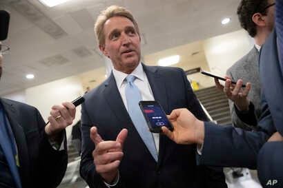 Sen. Jeff Flake speaks with reporters before he and Sen. Chris Coons try to bring up the legislation to protect special counsel Robert Mueller, at the Capitol in Washington, Nov. 14, 2018.