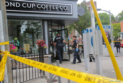Police officers enter a coffee shop damaged by gunfire while investigating a mass shooting on Danforth Avenue in Toronto, Canada, July 23, 2018.