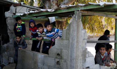 Palestinian boys watch near the a Hamas site after it was targeted in an Israeli airstrike in Gaza, March 26, 2019.