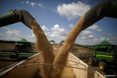 FILE - Harvesting machines are in operation during the opening ceremony of the Grain Harvest in Caseara, Brazil, Feb. 15, 2018.