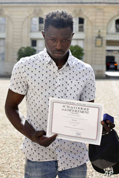 Mamoudou Gassama, 22, from Mali, displayed a certificate of courage and dedication signed by Paris Police Prefect Michel Delpuech as he leaves the presidential Elysee Palace after his meeting with French President Emmanuel Macron, in Paris, May, 28, ...