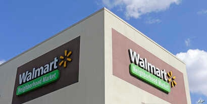 This Feb. 8, 2017, photo shows Wal-Mart signage at one of the company's neighborhood markets, in Hialeah, Florida.