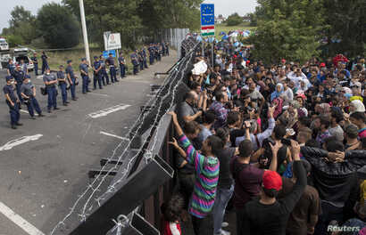 Migrants stand in front of a barrier at the border with Hungary near the village of Horgos, Serbia, Sept. 16, 2015.
