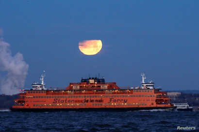 """The """"Super Blue Blood Moon"""" sets behind the Staten Island Ferry, seen from Brooklyn, New York, U.S., January 31, 2018."""