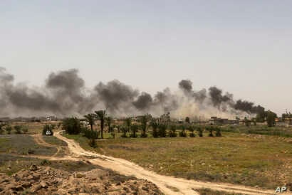 Smoke rises from Islamic State positions at the front line during fight against IS outside Fallujah, May 28, 2016.