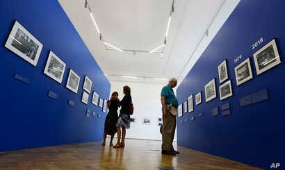 Visitors look at photographs on display documenting Jewish life in Poland from the 1970s, in Warsaw,  Aug. 8, 2018.