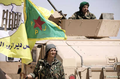 A female fighter from the Syrian Democratic Forces stands near a military tank in the village of Abu Fas, Hasaka province, Syria, Sept. 9, 2017. Abu Fas was the site of a triple car bomb blast Oct. 12, 2017, by Islamic State suicide attackers.