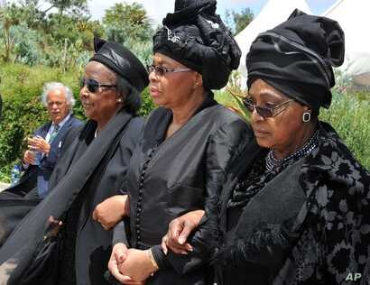 Winnie Madikizela-Mandela, right, Nelson Mandela's former wife, and Nelson Mandela's widow Graca Machel, centre, walk from the funeral service to the burial site of  former South African President Nelson Mandela in Qunu, South Africa, Sunday, Dec. ...