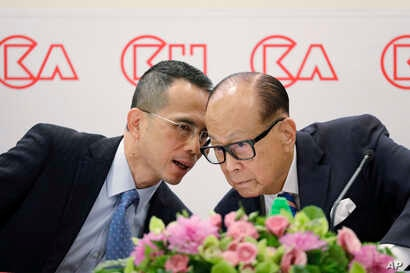 Hong Kong tycoon Li Ka-shing, right, chairman of CK Hutchison Holdings company, chats with his son, co-managing director Victor Li, at a press conference to announce the company's annual results in Hong Kong, March 16, 2018.