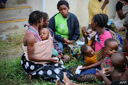 Displaced people get food and drink after arriving at the airport of the coastal city of Beira in central Mozambique on March 19, 2019, which was hit by Cyclone Idai.