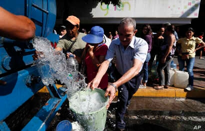 People collect water from a truck that delivers water during rolling blackouts, in Caracas, Venezuela, March 12, 2019.