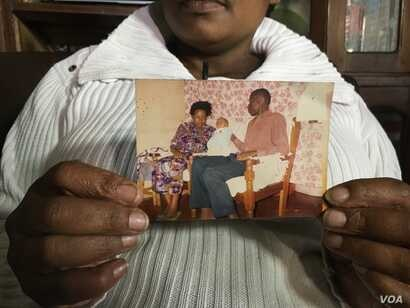 Pamela Olum holds up a picture of herself with her husband and their first-born child. Lawrence Olum was one of the 213 who died in the 1998 bomb attack in Nairobi, Kenya. (M. Yusuf/VOA)
