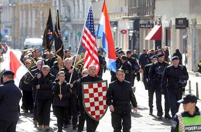 A group of right-wing radicals wave Croatian and US flags as they march through downtown Zagreb, Feb. 26, 2017.