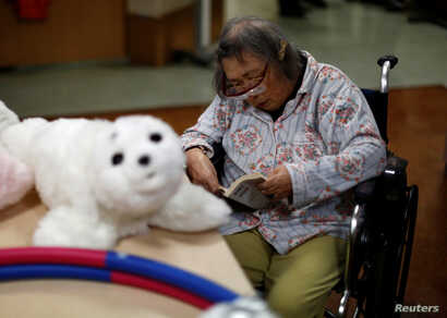 A resident reads a book during a session with 'AIBO'a pet dog robot and 'PARO' a robot seal at Shin-tomi nursing home in Tokyo, Japan, Feb. 2, 2018.