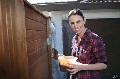 New Zealand Labour Party leader Jacinda Ardern paints her fence at home in Auckland, New Zealand, Sept. 23, 2017.