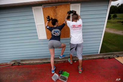 Haley Sensebe, left, and Bernard Oser board up their home in Violet, La., in preparation for Hurricane Nate, expected to make landfall on the Gulf Coast, Oct. 7, 2017.