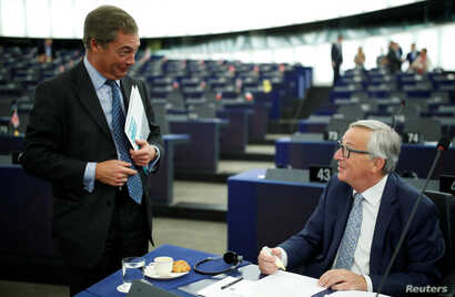 European Commission President Jean-Claude Juncker, right, talks with Nigel Farage, United Kingdom Independence Party member and member of the European Parliament, ahead of debate at the parliament in Strasbourg, France, Sept. 13, 2017.