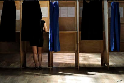 A woman prepares her ballot in a voting booth in the first round of parliamentary elections, in Lyon, central France,  June 11, 2017. French voters go to the polls Sunday in the second round to choose lawmakers in the lower house of parliament.
